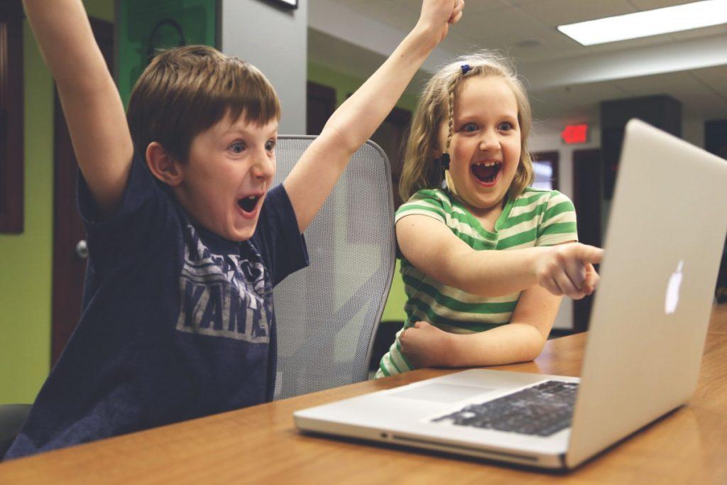 Mädchen und Junge vor Computer